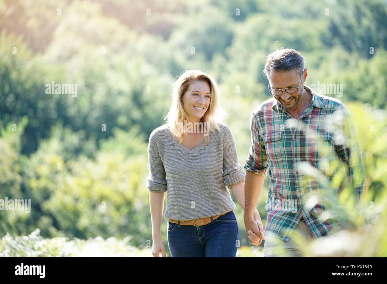 Happy mature couple walking in countryside on sunny day - Stock Image