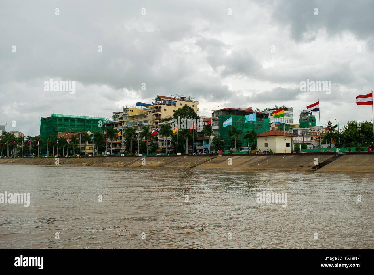 Globalisation example. A set of international flags of different countries flying on Tonle Sap riverfront Sisowath - Stock Image