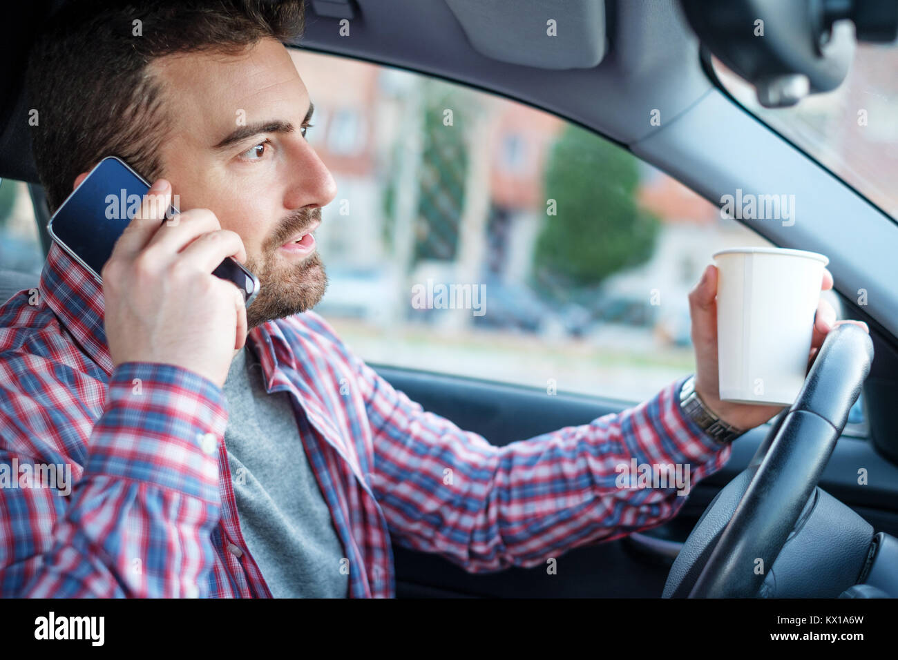 Man driving his car and using mobile phone - Stock Image