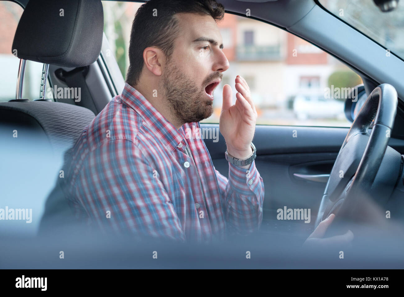 Bored and tired yawning man driving his car need a rest - Stock Image