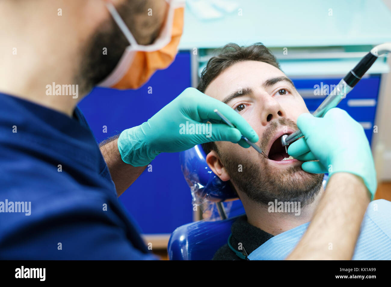 Dentist examining patient's teeth in clinic - Stock Image