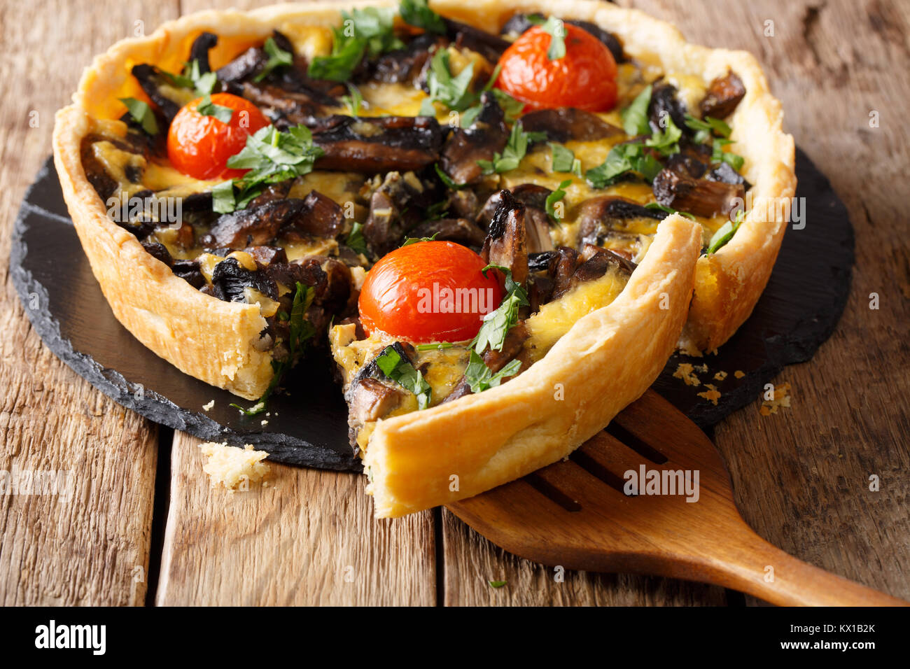 Sliced mushroom tart with cheese and tomatoes close-up on the table. horizontal - Stock Image