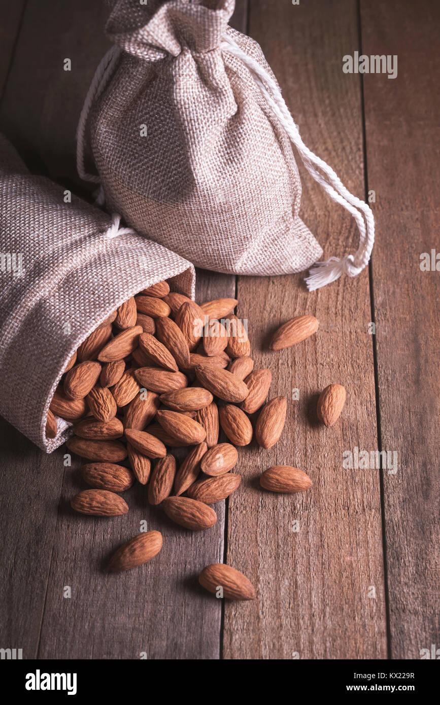 Almonds in hessian sack. - Stock Image