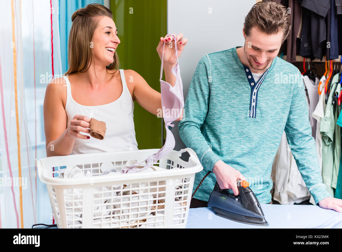 Young couple, woman and man, sharing housework and doing the lau - Stock Image