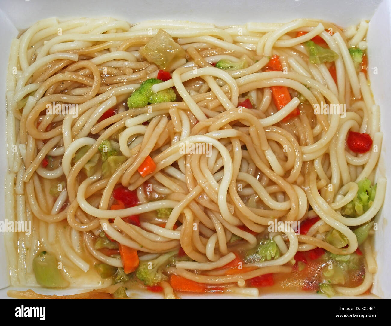 Cardboard container of noodles and vegetables that has been microwaved - Stock Image