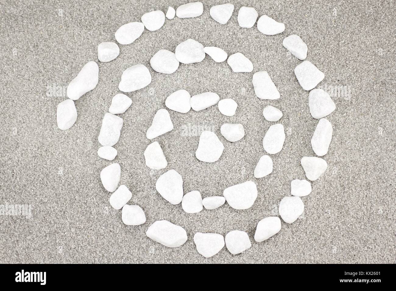 White pebbles arranged in a spiral - Stock Image