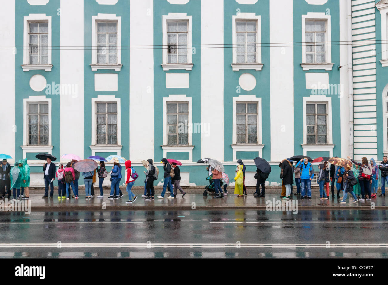 Tourists waiting in line for the Kunstkamera museum on a rainy day. Saint Petersburg, Russia. - Stock Image