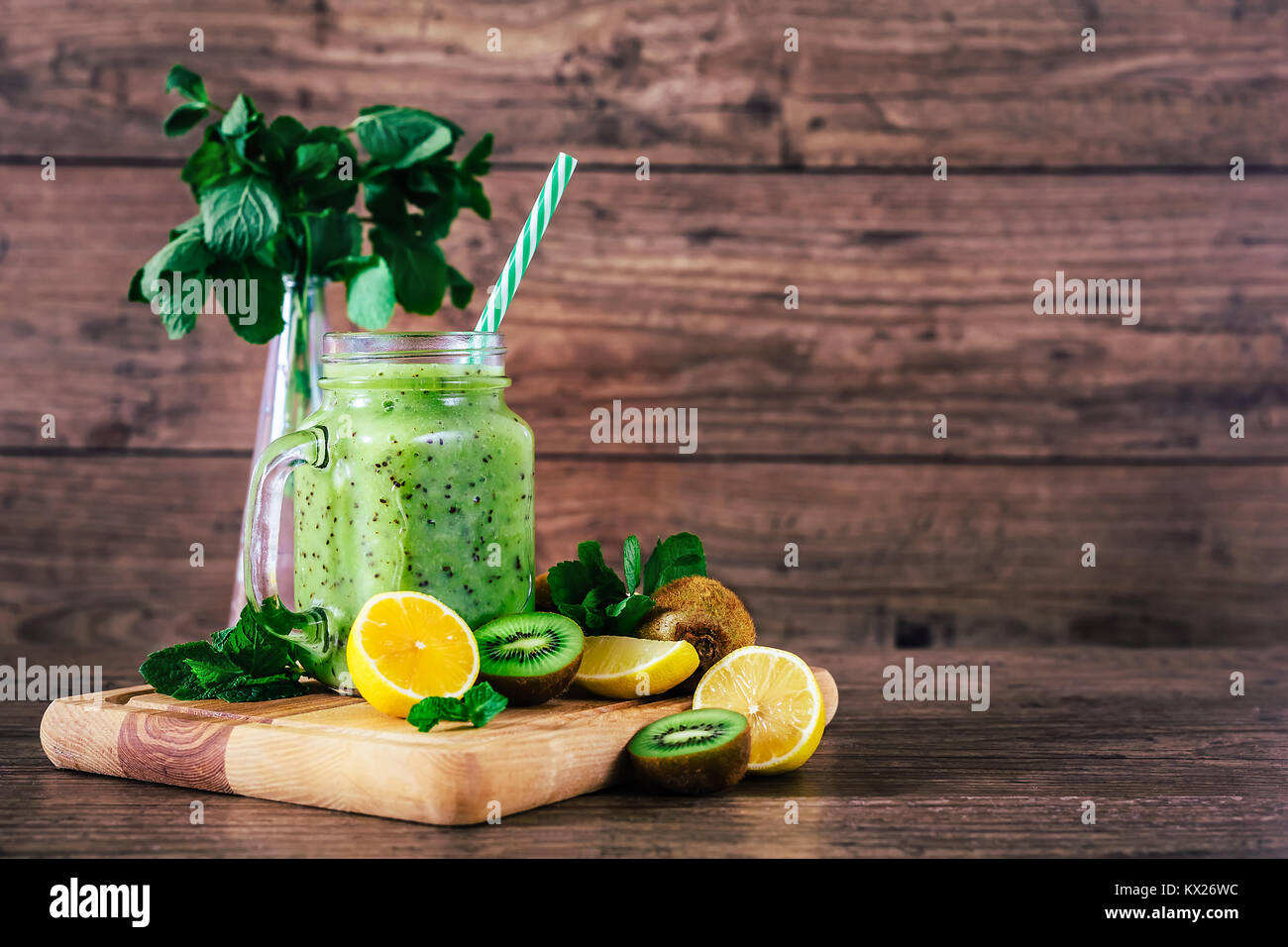 Delicious kiwi smoothie with mint in mason jar on table against dark wooden background. Healthy lifestyle concept - Stock Image