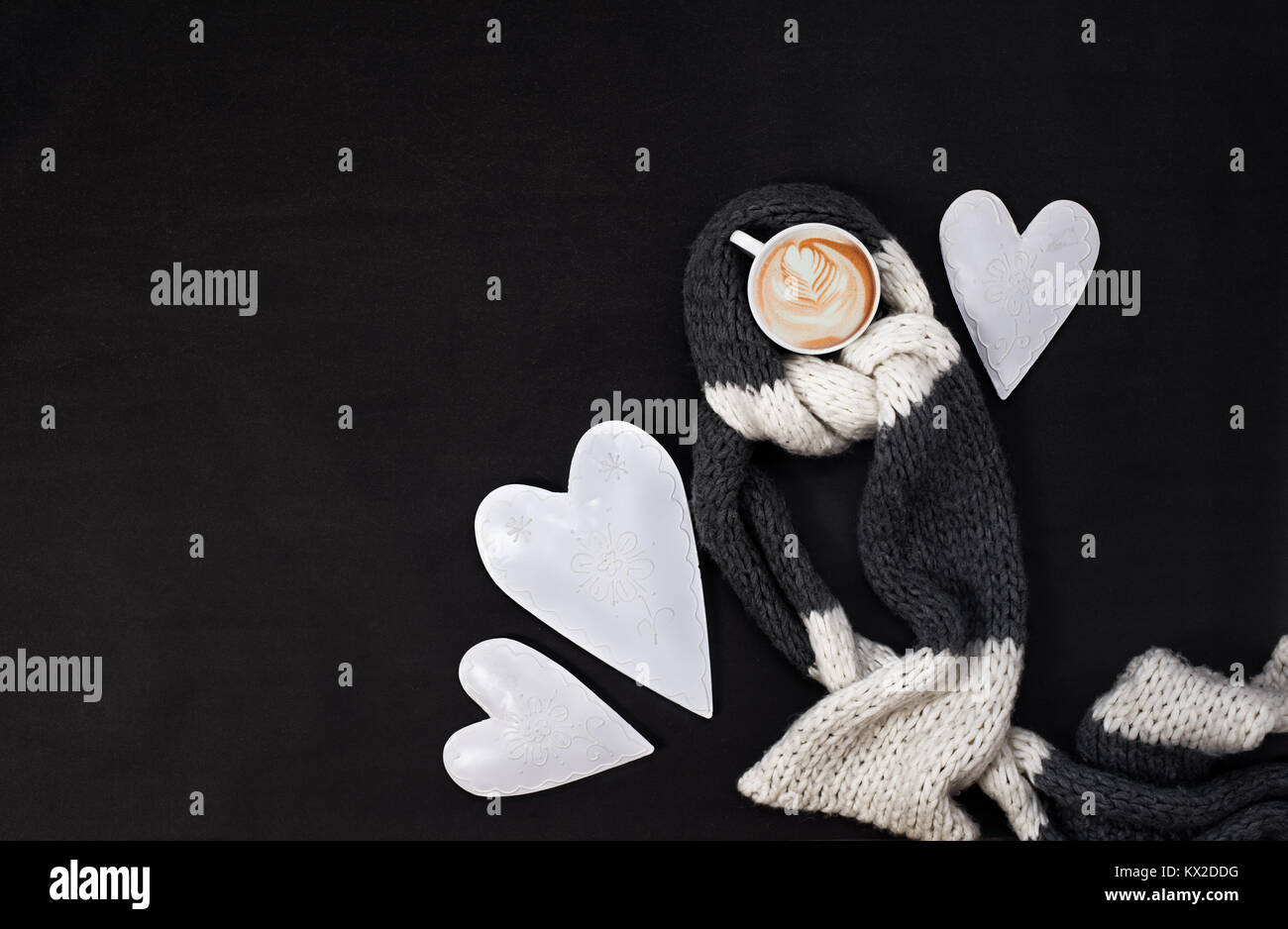 Valentine's day morning top view composition with hearts and a cup of cappuccino covered with wool scarf - Stock Image