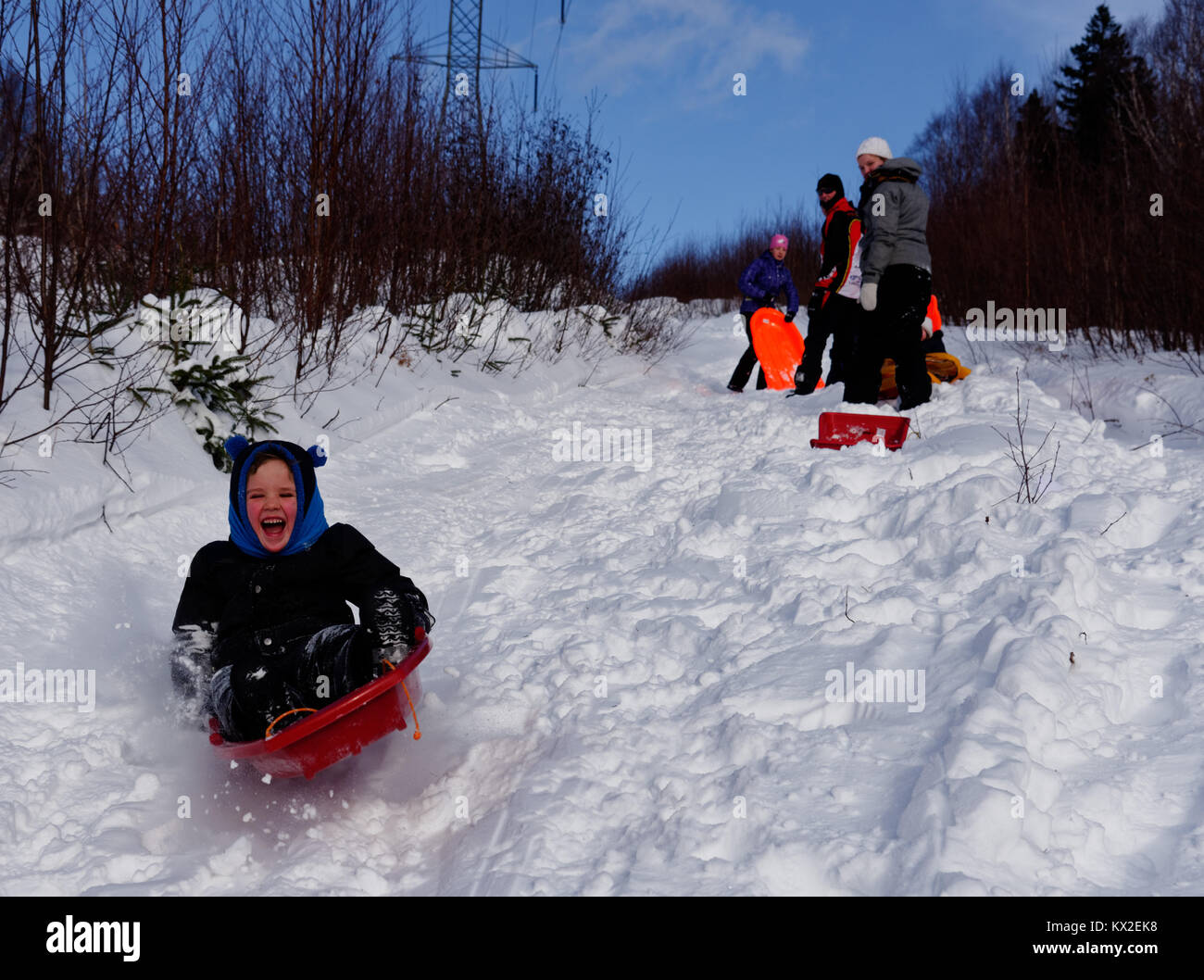 A laughing 5 yr old boy speeding on a sledge while the rest of the family look on - Stock Image