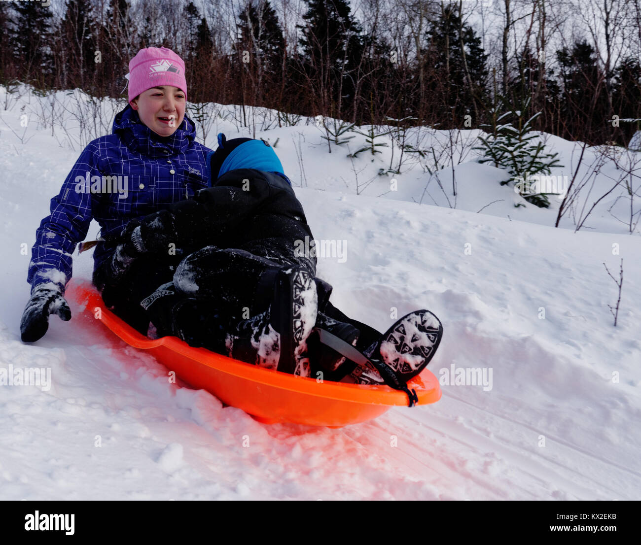 A teenager (18 yr old) in a sledge with a young child (5 yr old), looking nervous as its much faster than she thought - Stock Image