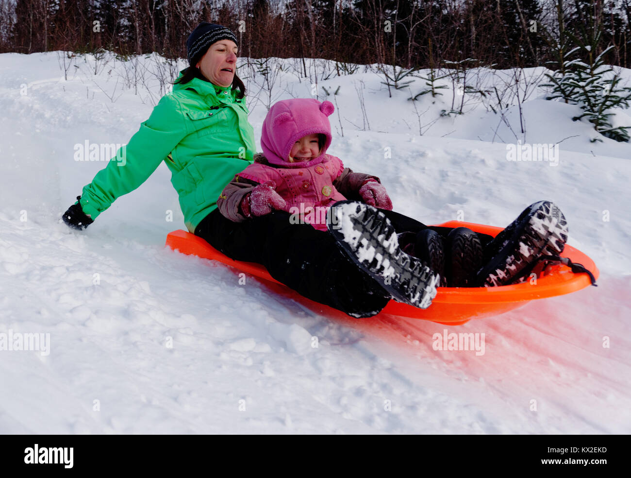An adult woman in a sledge with a little girl (3 yr old) looking nervous as its much faster than she thought - Stock Image