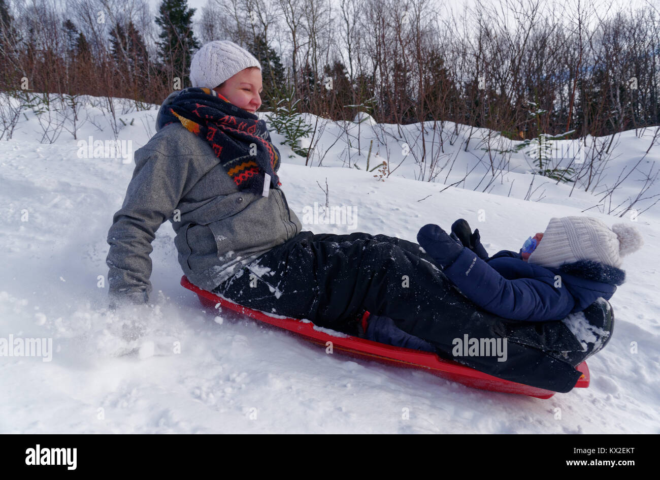 A smiling young mother sledging with her infant (1 yr old) daughter - Stock Image