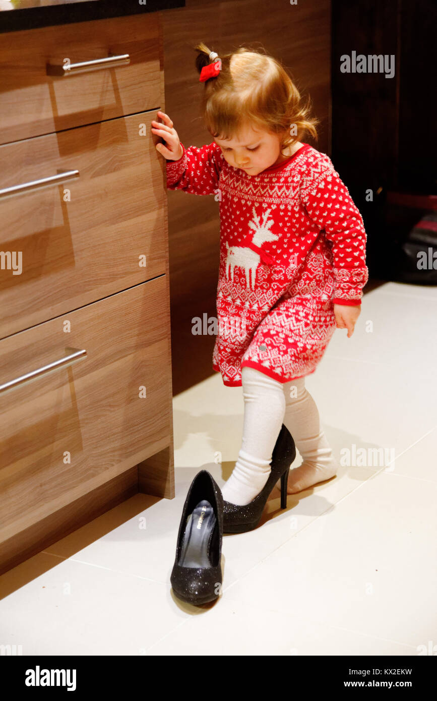 A young girl (18 months) trying on a pair of ladies high-heeled shoes - Stock Image