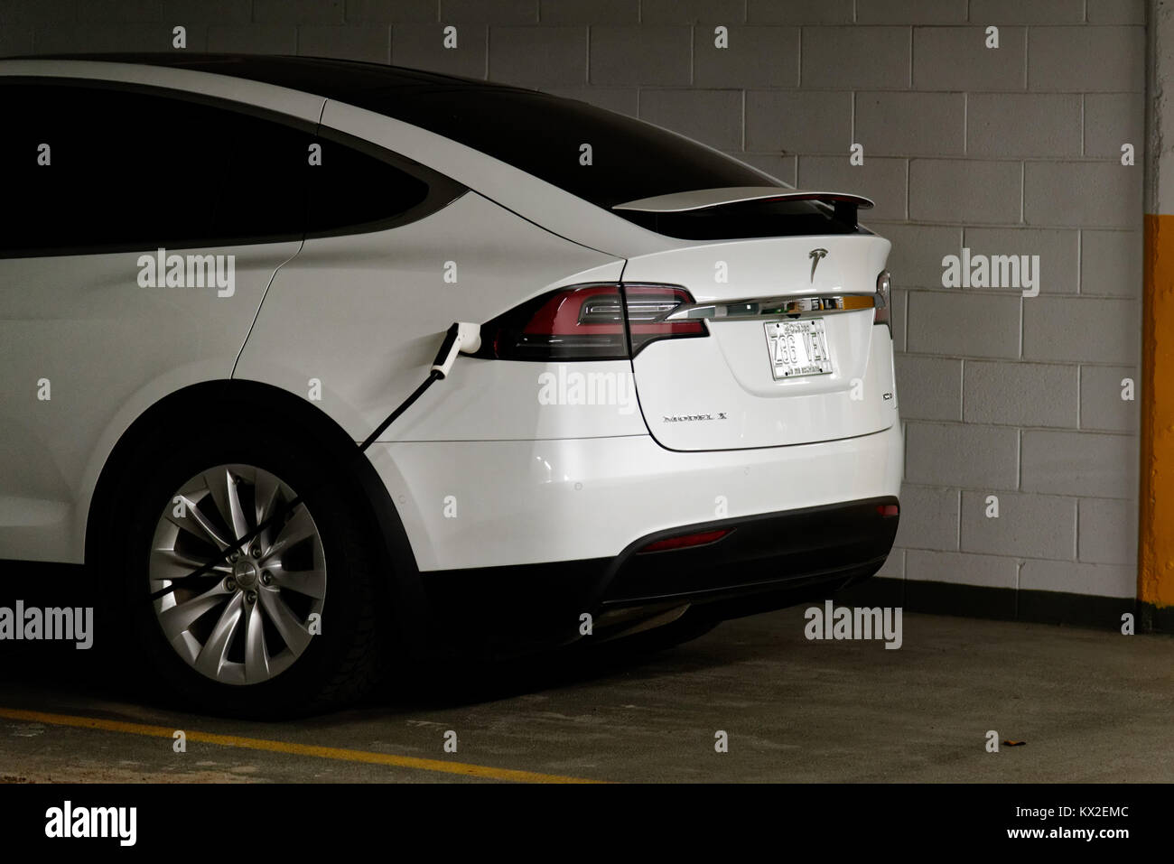 Tesla Model X electric car recharging in a car park in Montreal, Quebec - Stock Image