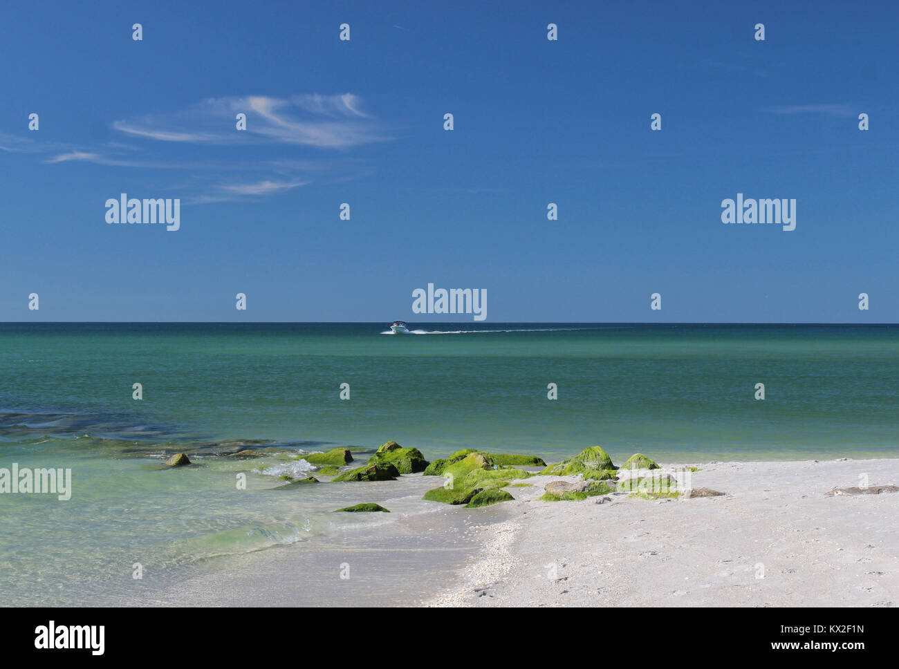Landscape of a rocky and sandy beach with boat cruising past at Stump Pass Beach State Park Florida - Stock Image