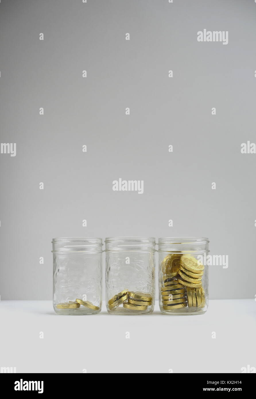 Three glass jars filled with gold coins and plenty of copy space. Investment, finance, revenue and savings concept. - Stock Image