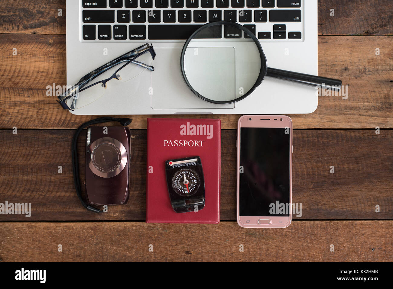 notebook laptop, camera, passport, compass, smartphone on a wooden table. travel information concept - Stock Image