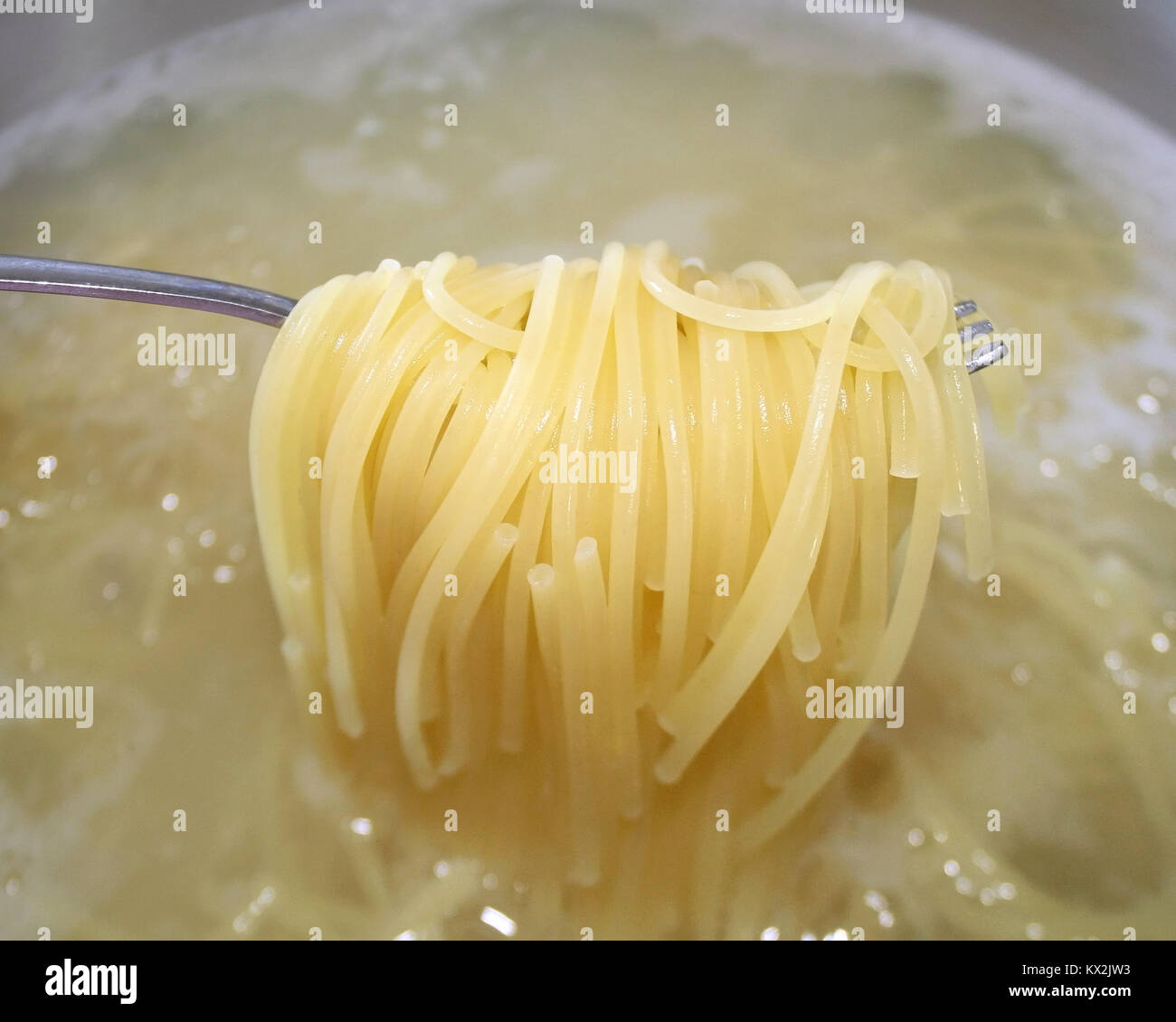 Cooked pasta noodles being lifted out of pot of boiling water with fork - Stock Image