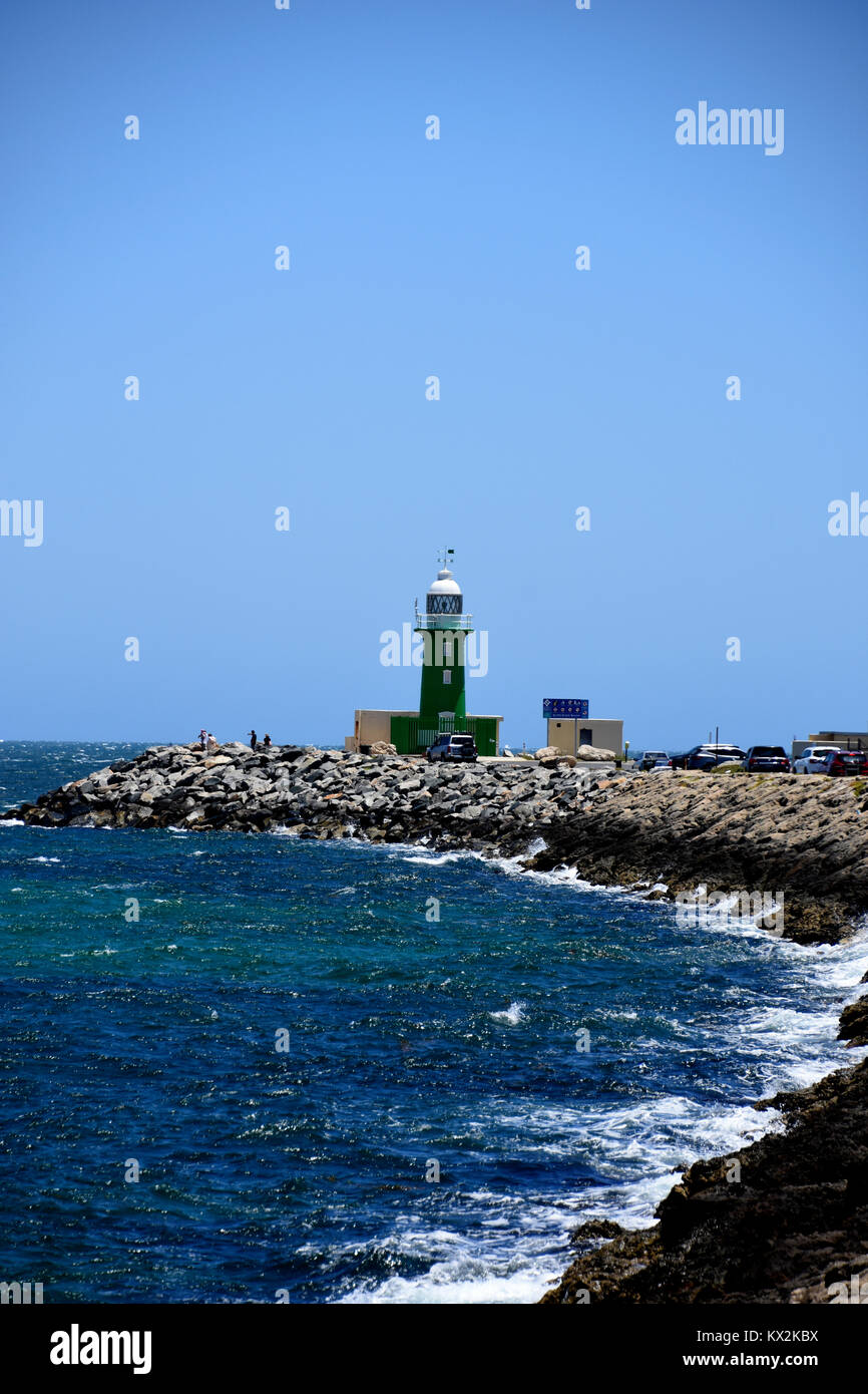 Starboard green lighthouse on a breakwater at the entrance to Freemantle harbour - Stock Image