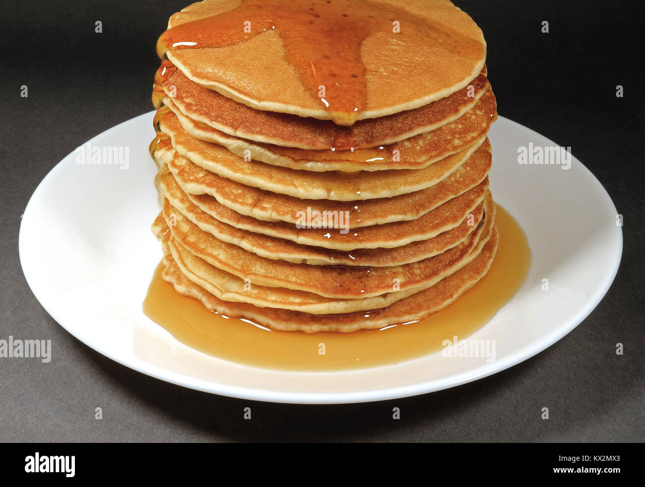 Pile of Fresh Homemade Pancakes Served with Maple Syrup on White Plate, Isolated on Black Background Stock Photo