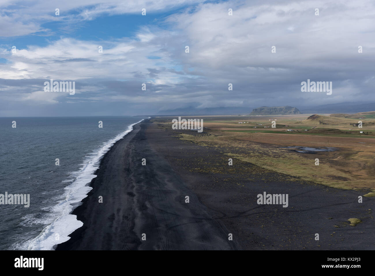 Black sands and some distant land - Stock Image