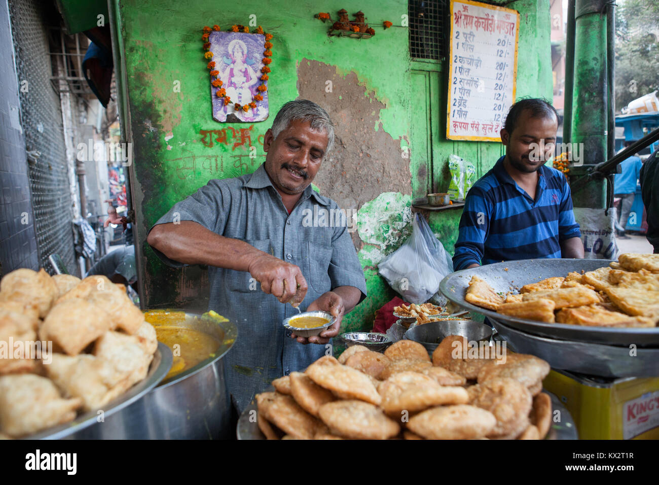 A vendor serves a plate of kachori at a food hotel in the old city of Delhi, India - Stock Image