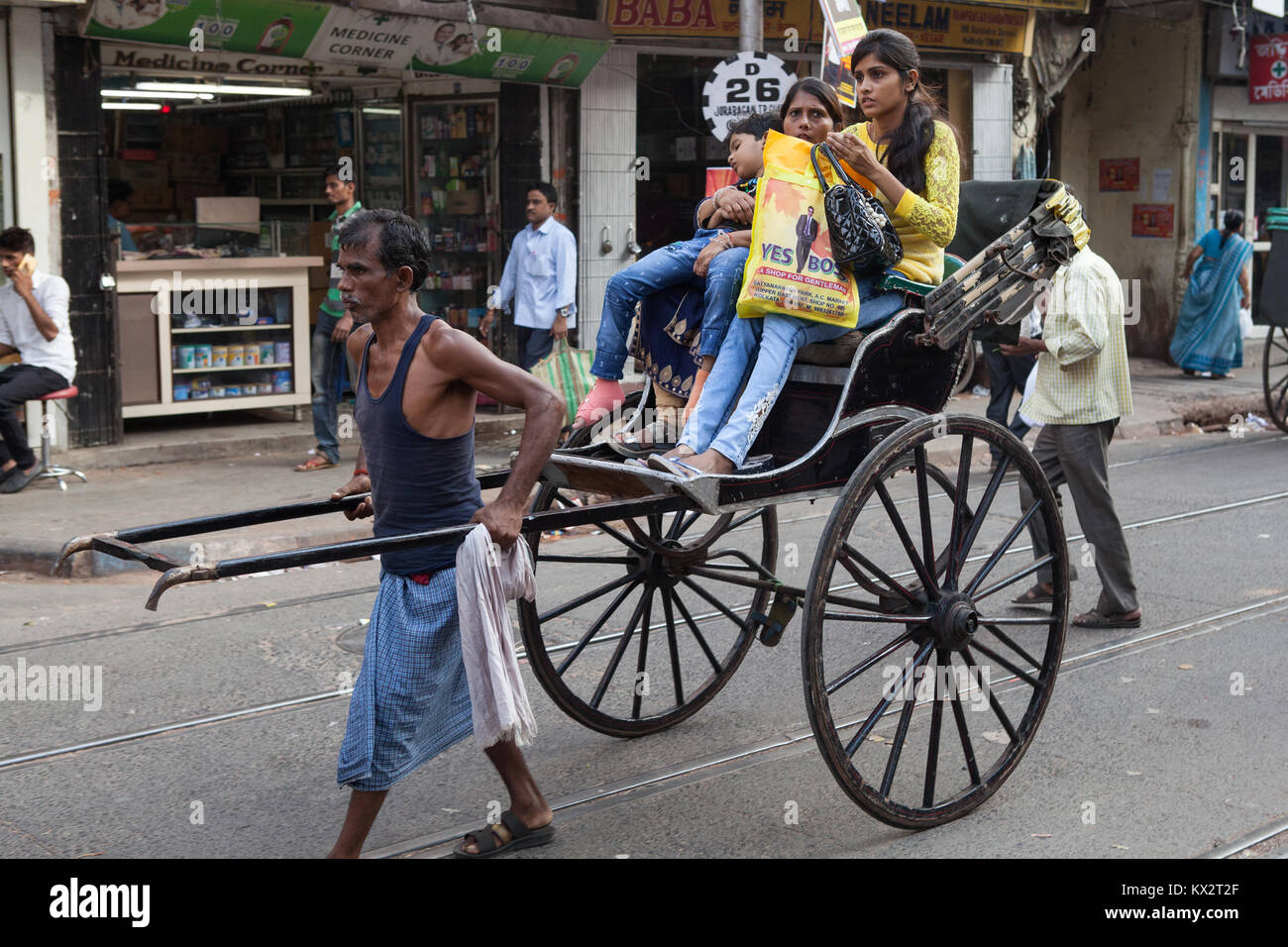 A rickshaw driver carries passengers through the streets of Kolkata, India - Stock Image