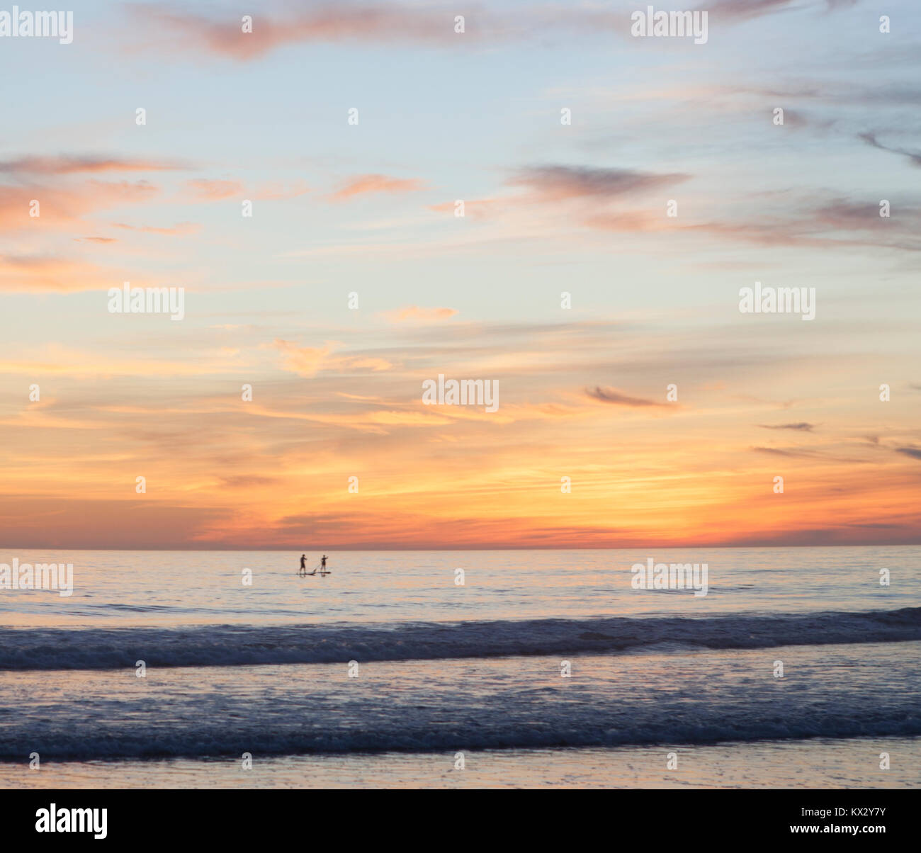 Two people on stand up paddle boards in middle of ocean at sunset. - Stock Image