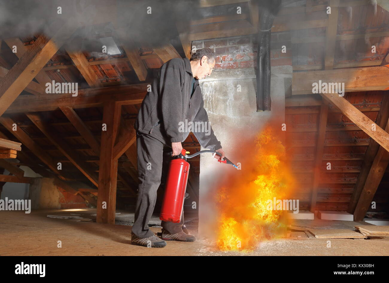 A Man with fire extinguisher fighting agains fire in his house - Stock Image