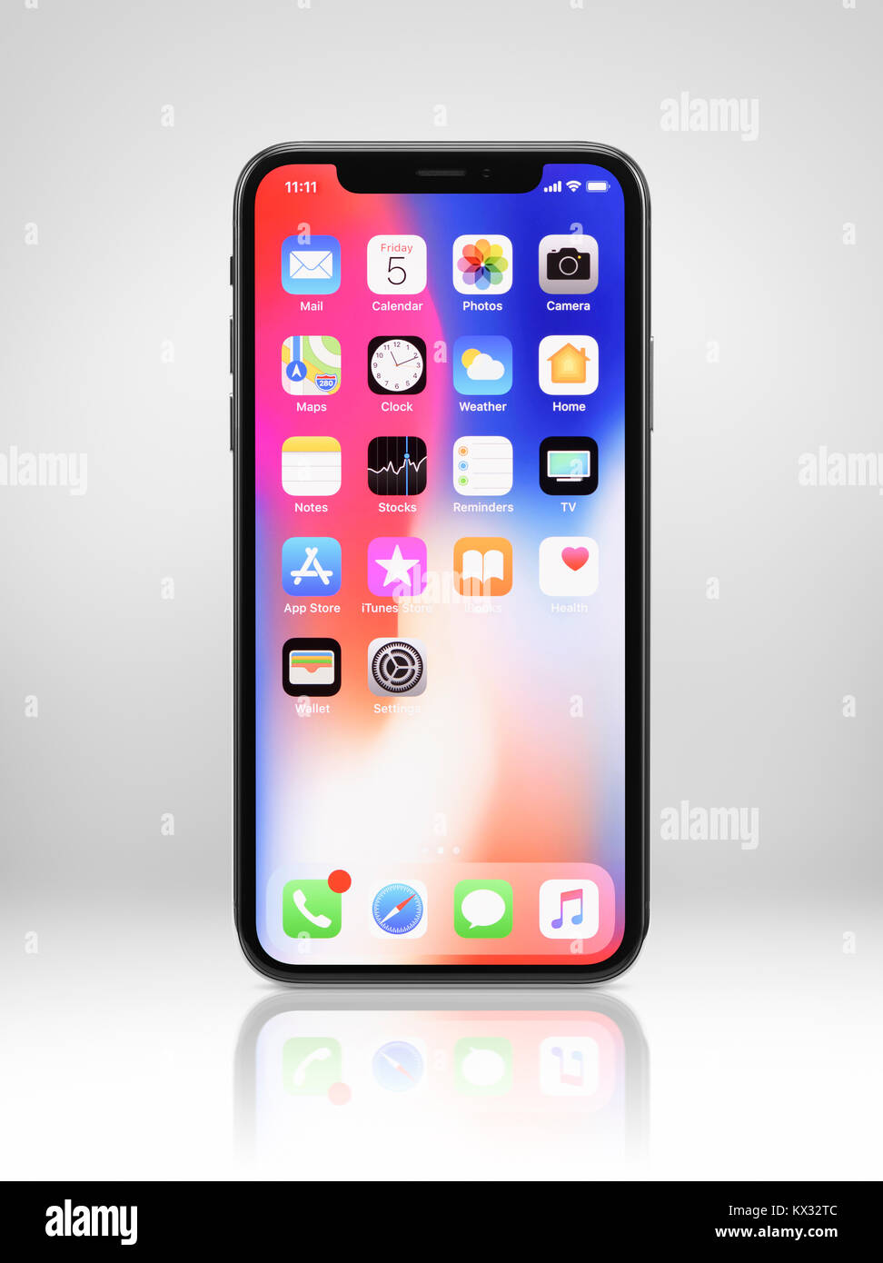 Apple iPhone X, large screen smartphone, with colorful desktop on its display. The phone is isolated on light gray - Stock Image