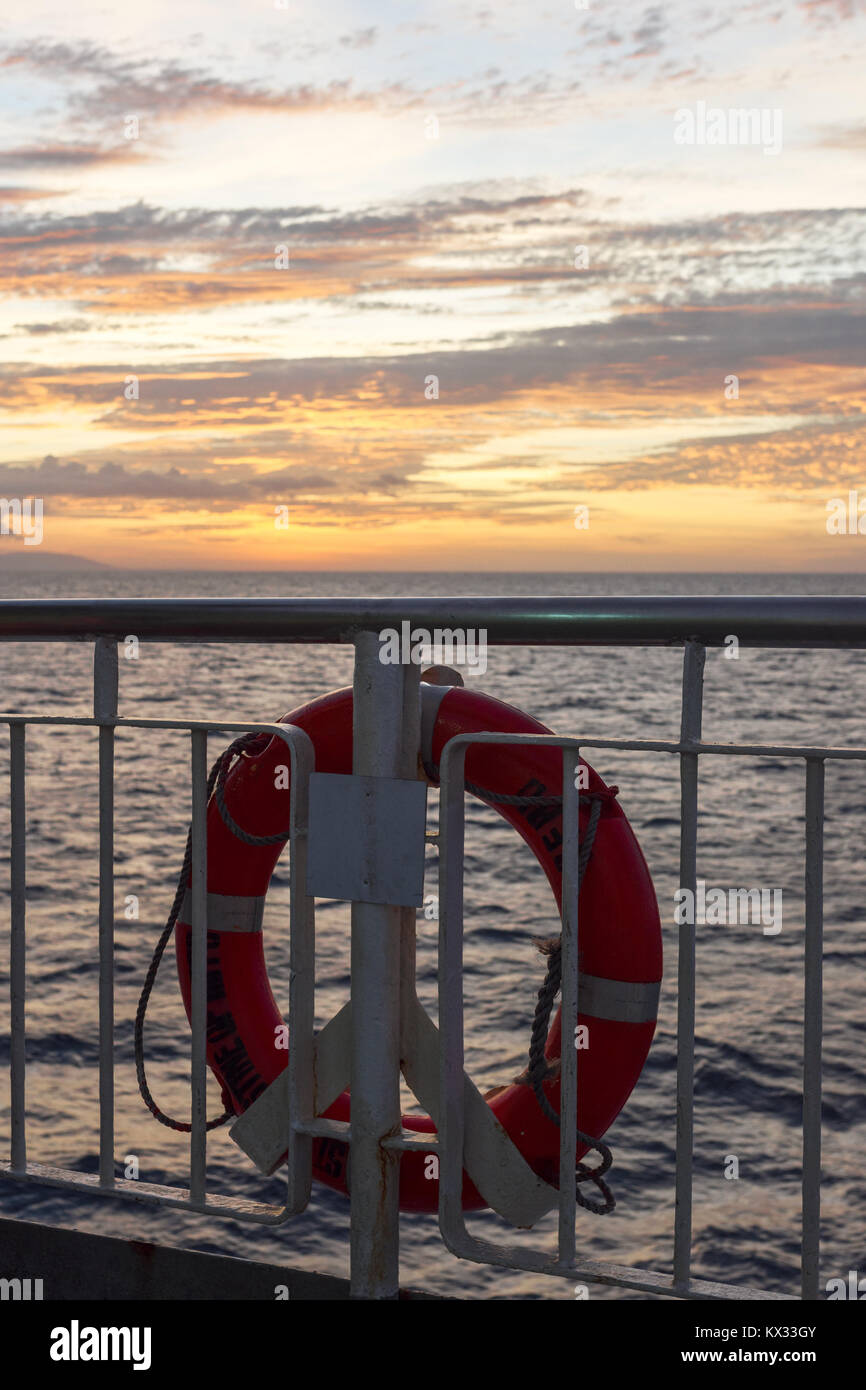 A bright orange lifebuoy life ring attached to the hand rail of a ship crossing between islands in the Philippines Stock Photo