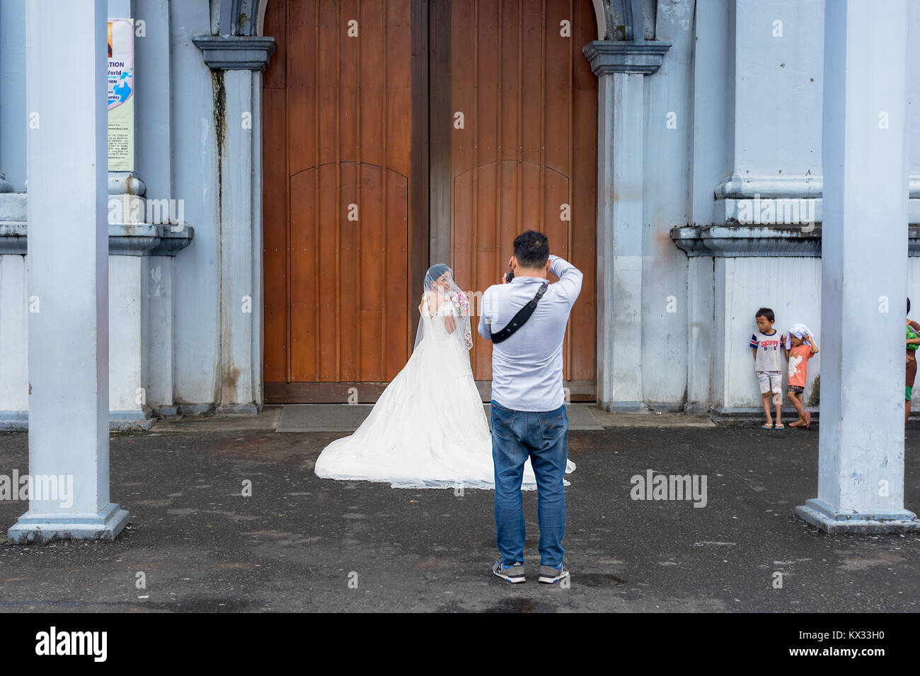 A wedding photographer taking the final photos before the bride in her white wedding dress enters the church whilst - Stock Image
