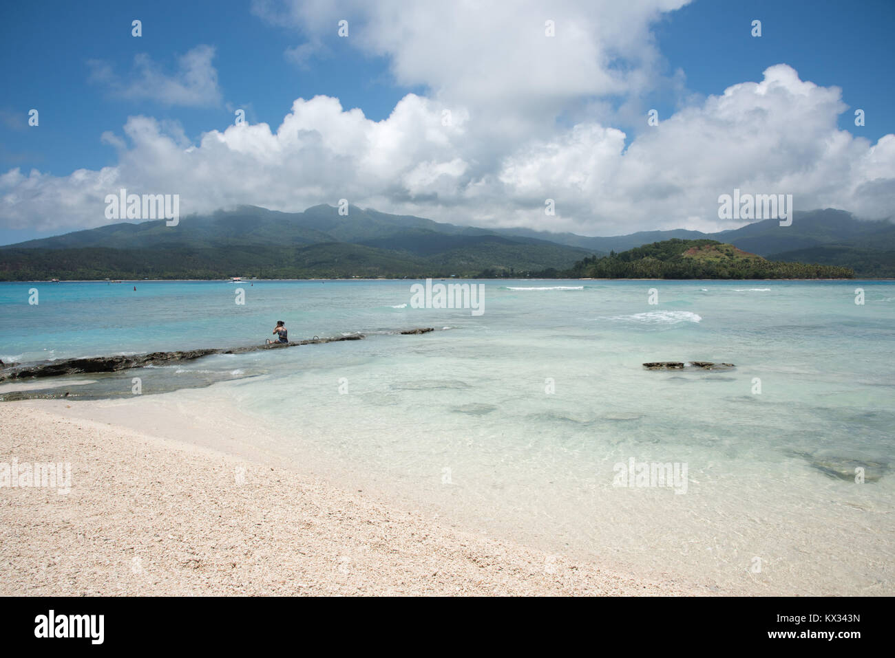 MYSTERY ISLAND, VANUATU, PACIFIC ISLANDS: DECEMBER 2,2016:  One woman sitting on coastal rock in the ocean off the - Stock Image