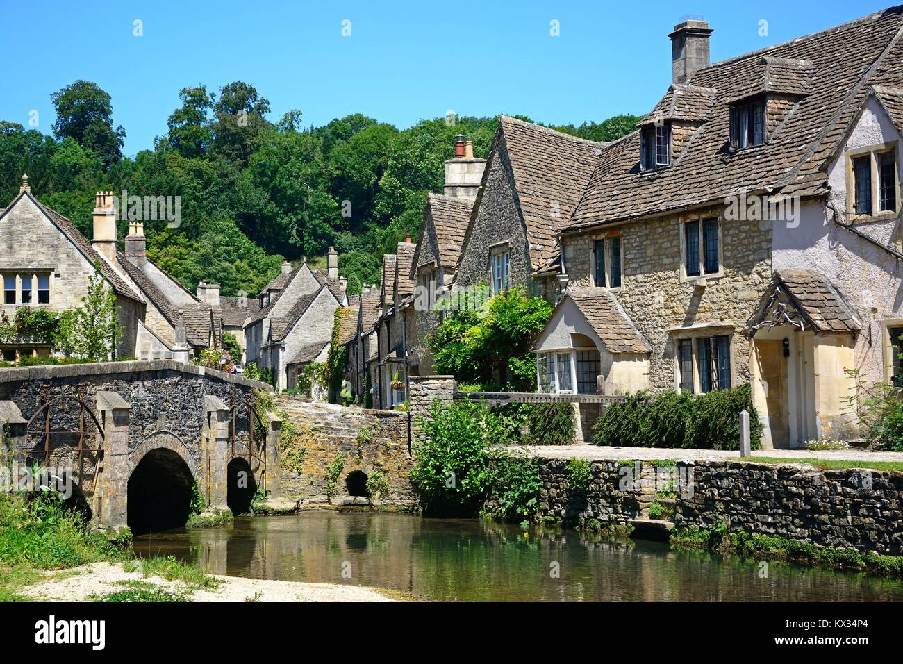 Stone bridge over the river Bybrook with cottages to the rear, Castle Combe, Wiltshire, England, UK, Western Europe. - Stock Image