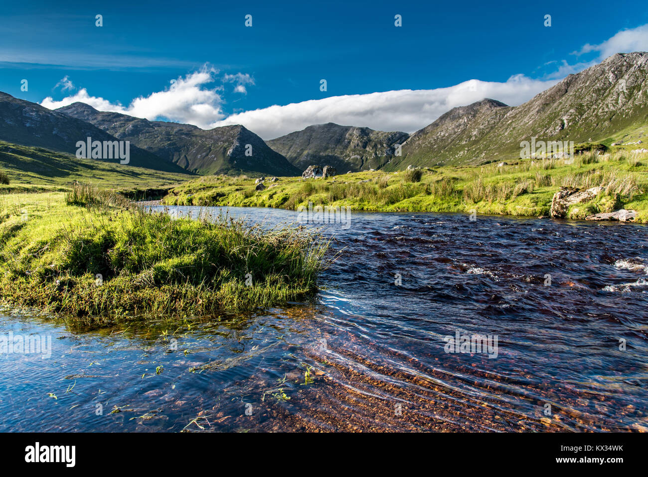 Connemara landscape in Ireland: a river flows amid the meadows in front of the majestic Twelve Bens mountains - Stock Image