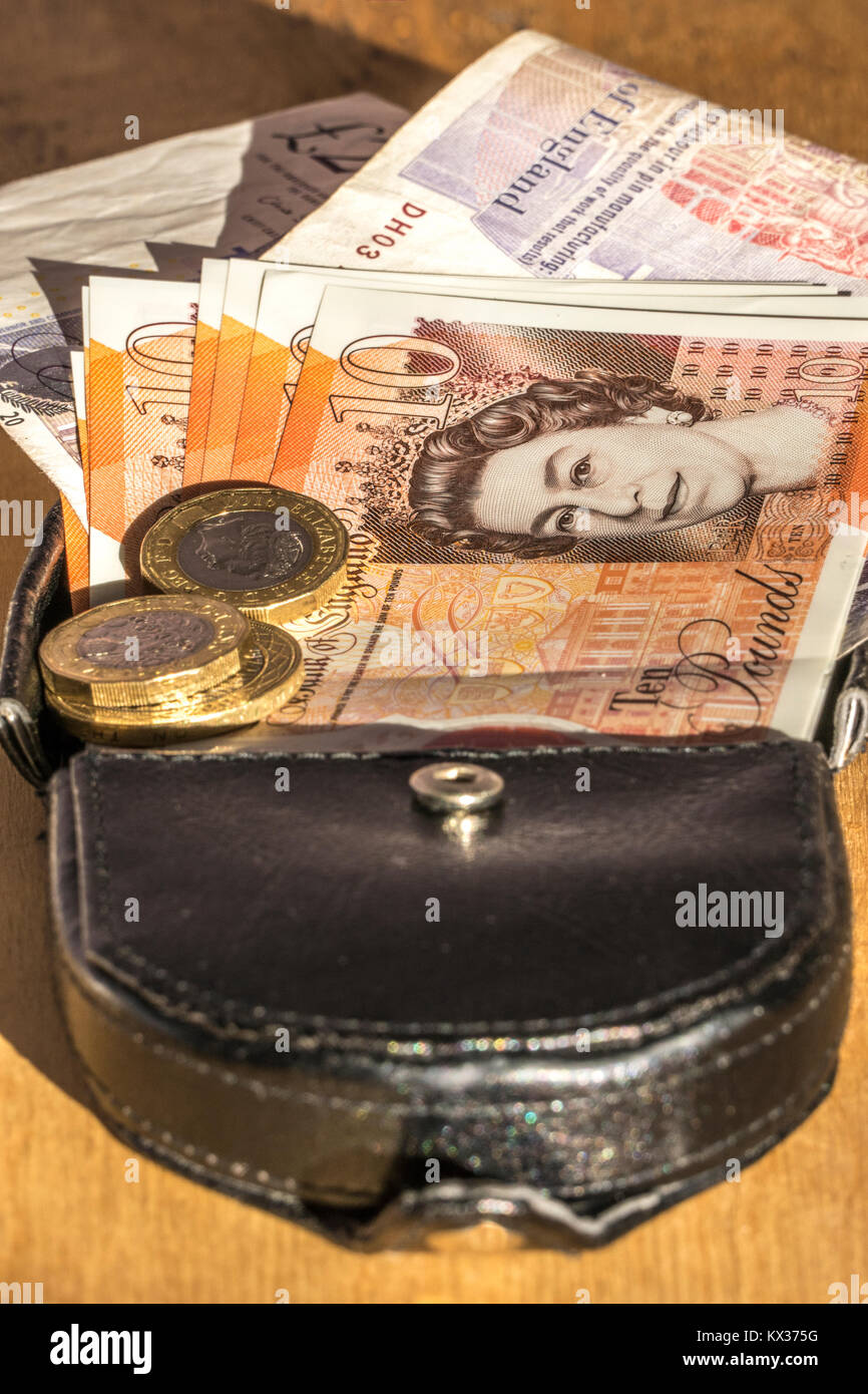 New £10 notes and £1 coins, pound / pounds sterling currency, on a leather purse. Concept of British / UK money, Stock Photo
