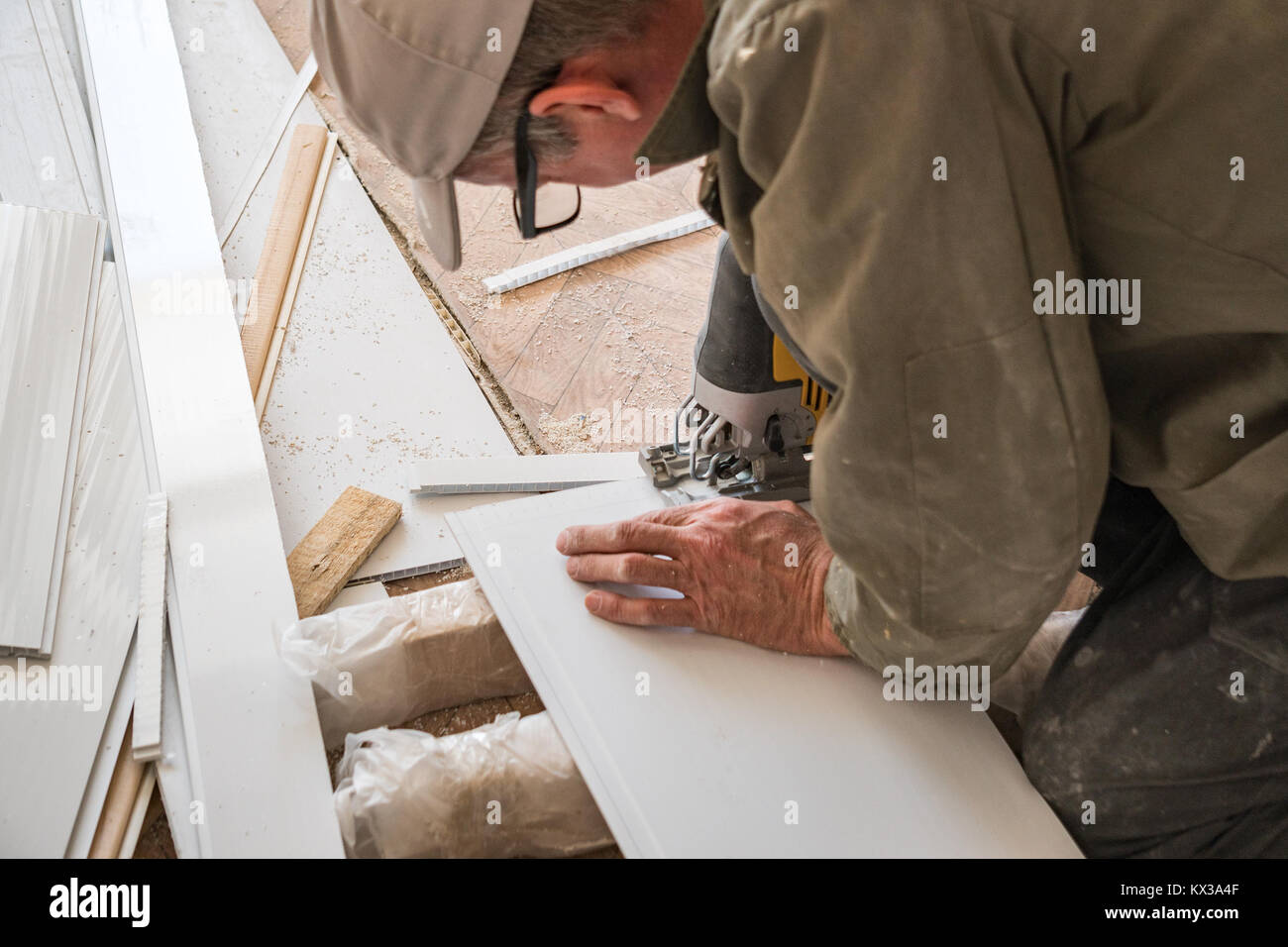 Builder works with white plastic parts - Stock Image
