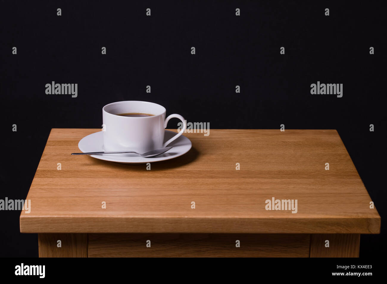 An image of a cup of black coffee sitting on an oak coffee table - Stock Image