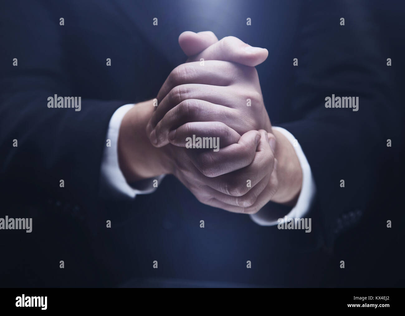 Praying hands on black backgroun - Stock Image