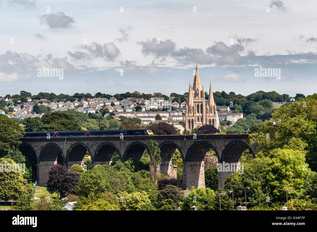 Truro, Cornwall, UK. A First Great Western train crosses Carvedras Viaduct (1902) in front of Truro Cathedral. The - Stock Image