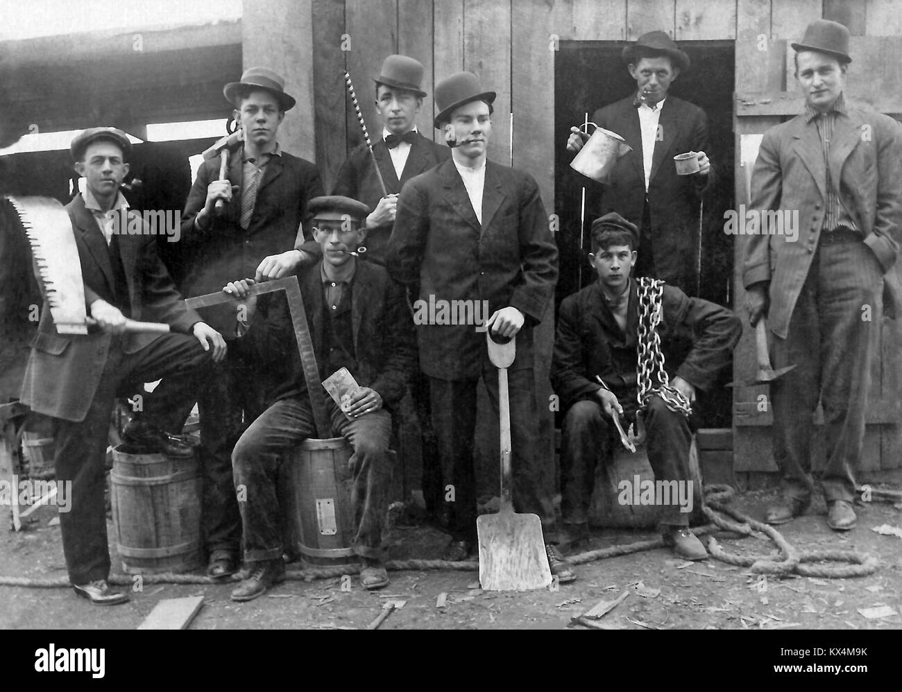 8 different trade workers posed with their tools, circa 1910, vintage photograph. - Stock Image