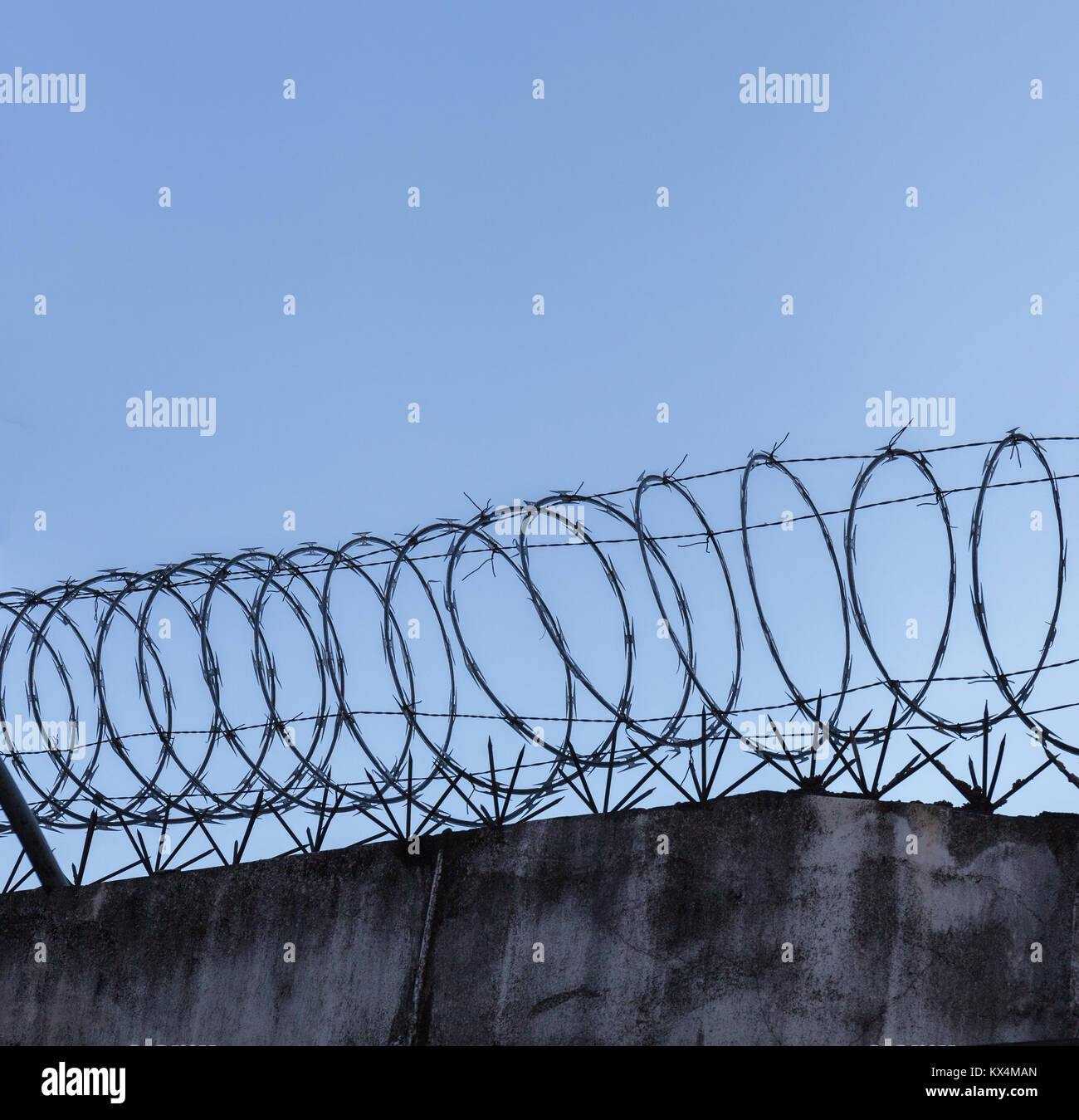 Barbed wire spiral on top of rough high stone wall on the sky background - Stock Image