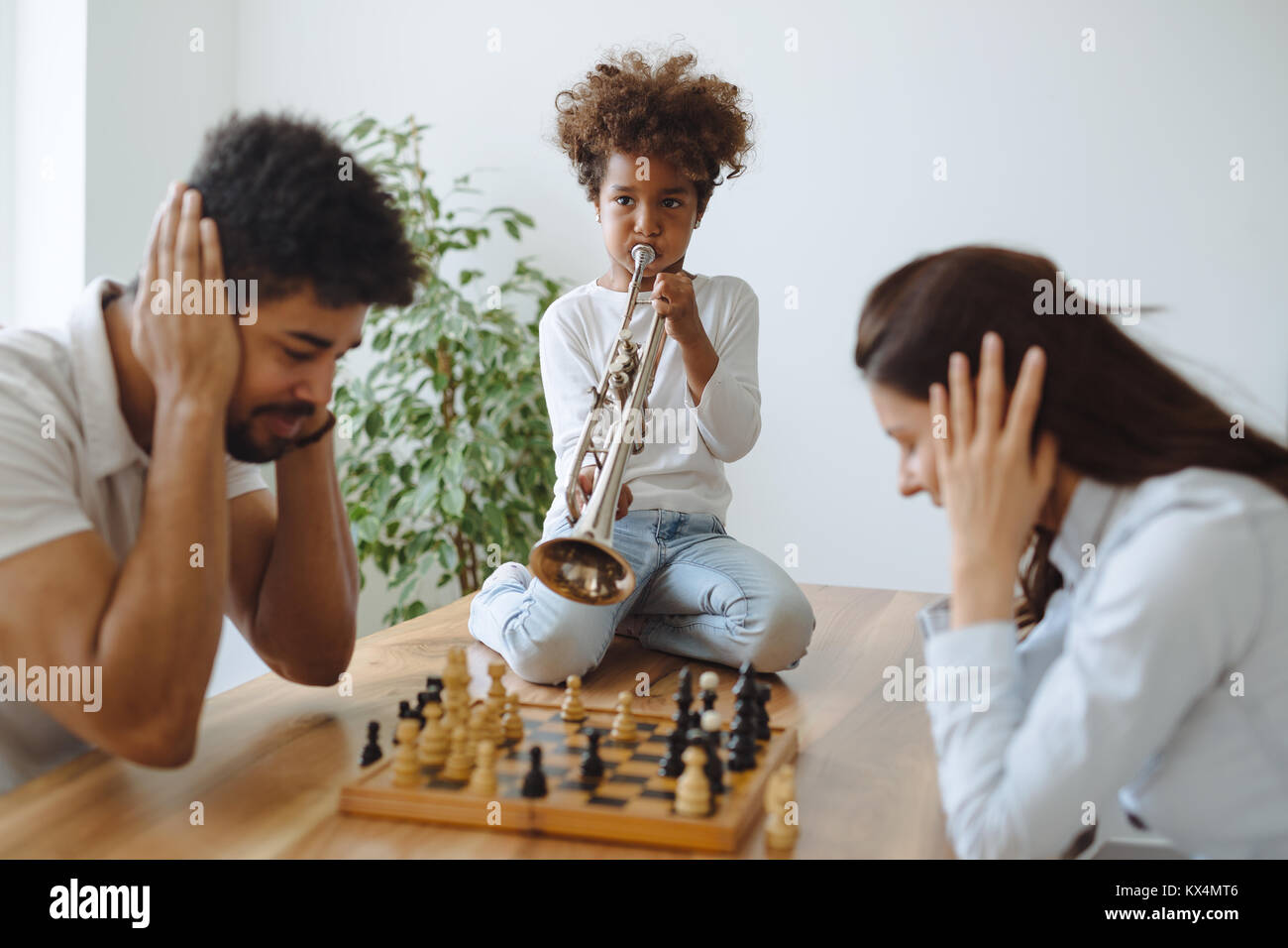Mother and father trying to play chess while their child plays trumpet - Stock Image