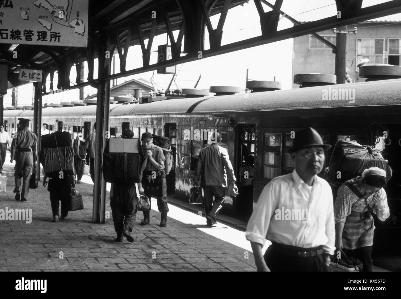 Railway station platform in Japan, 1966. Note the heavily-laden porters. Stock Photo