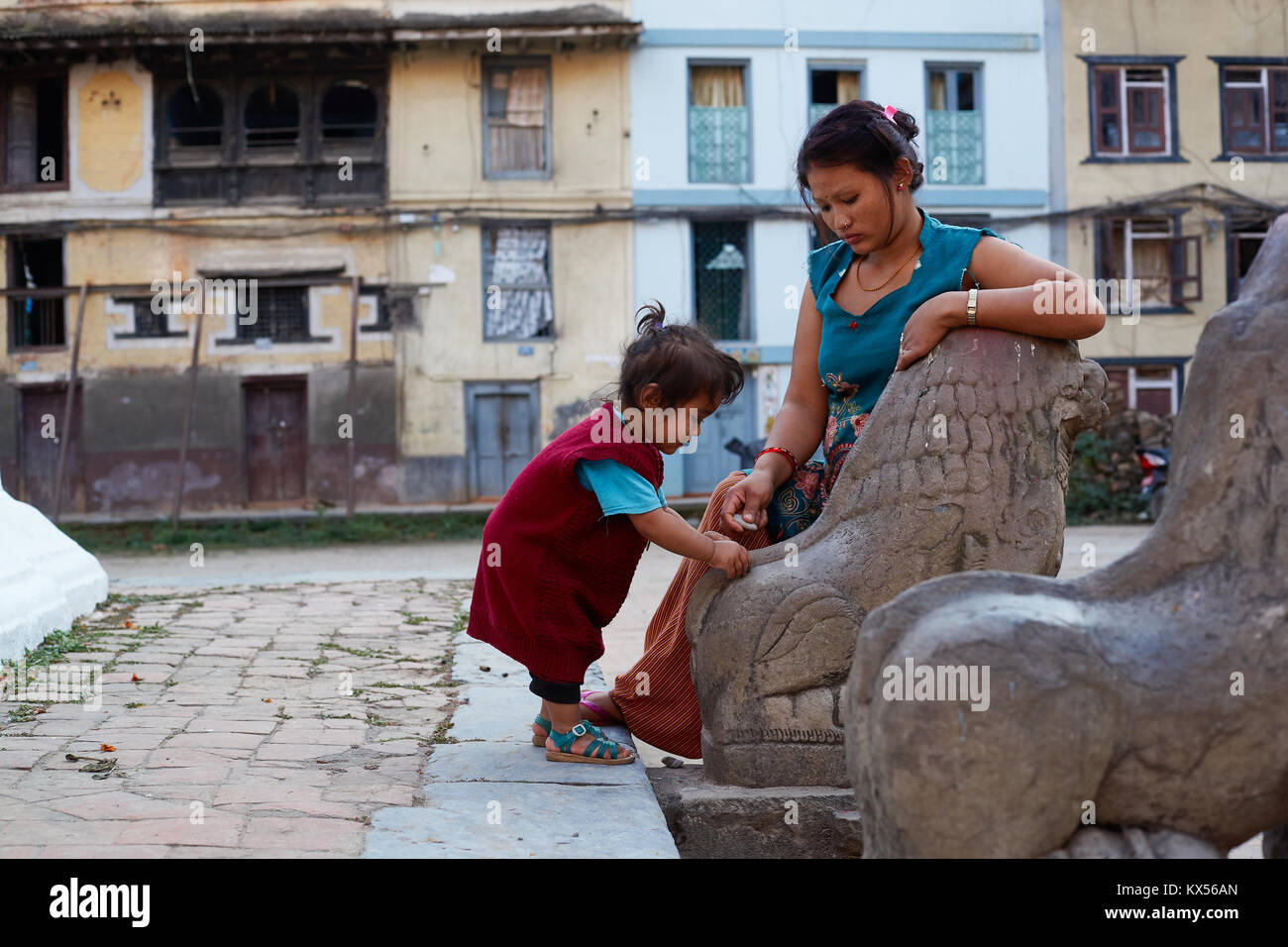 Nepali woman and baby playing with lion statue, Kathmandu, Nepal - Stock Image