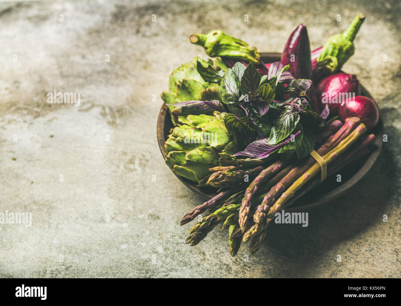 Flat-lay of green and purple vegetables on plate, concrete background Stock Photo