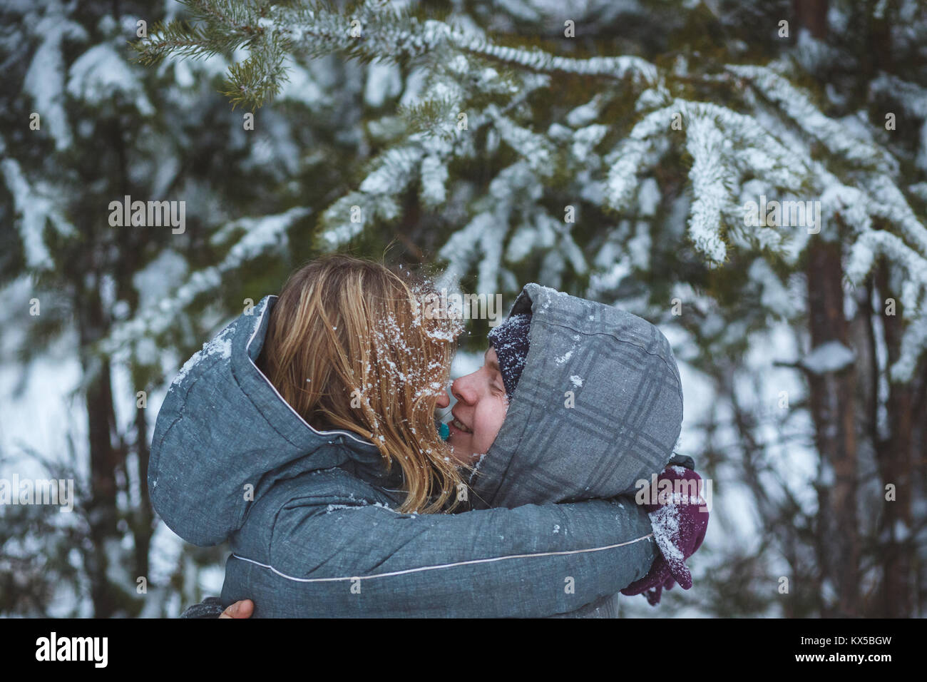 Happy snow covered couple kissing under fir branches in winter forest. Concept healthy romantic holidays on fresh - Stock Image