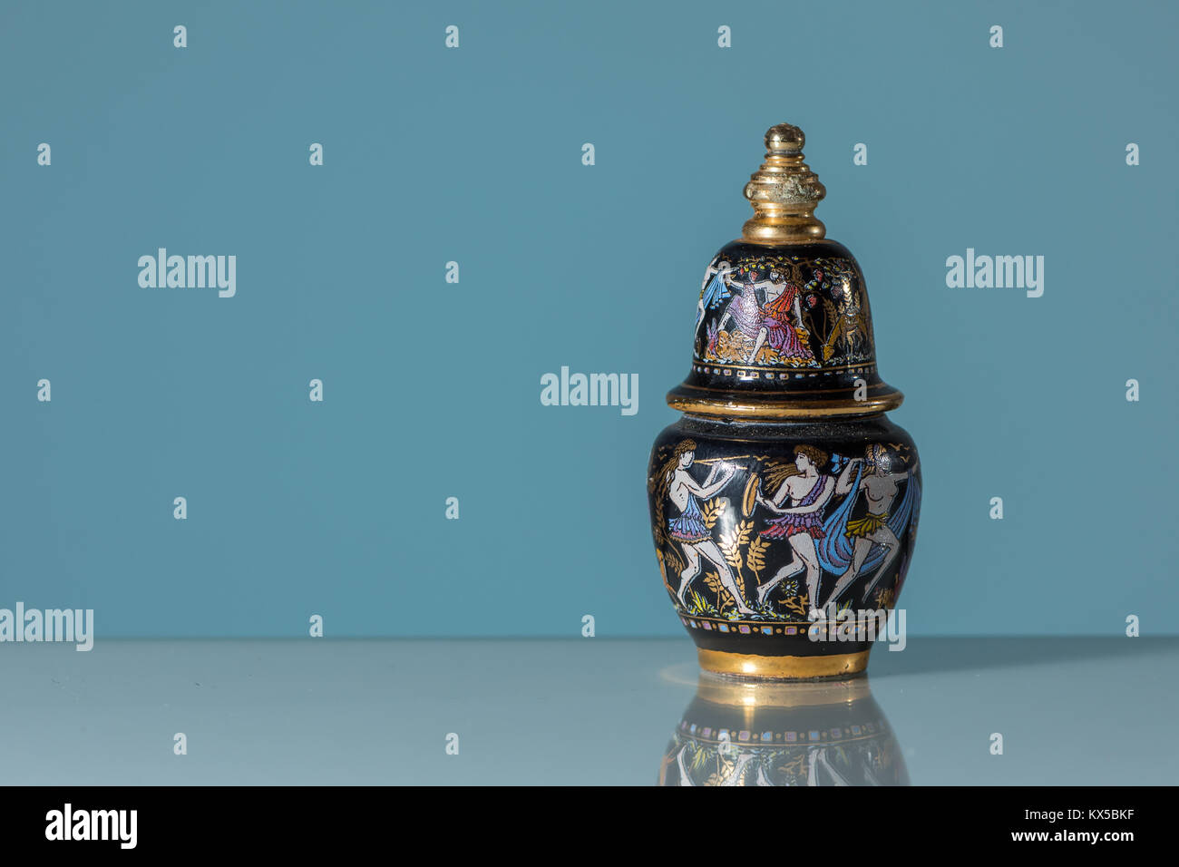Closeup of an Old black golden perfume flask with paintings - Stock Image