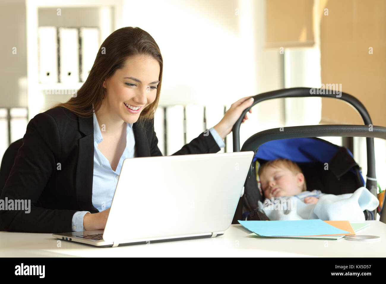 Happy single mother working on line and taking care of her baby at office - Stock Image